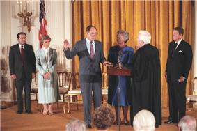 An elderly white haired man in judicial robes swears in a middle-aged man in a suit as several people look on.