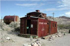 An abandoned wooden rail car rests on a bed of gravel. A large, rusting, cylindrical tank is nearby, among low bushes. Barren, striated hills can be seen in the distance. Lettering on the car says,