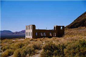 A roofless two-story masonry building rests in a setting of low shrubs and gravel under a cloudless blue sky. The building has many window openings but no glass. A mountain or hill is nearby, and a separate mountain range is visible in the distance.