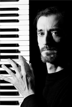 Bearded white male holding electric piano keyboard