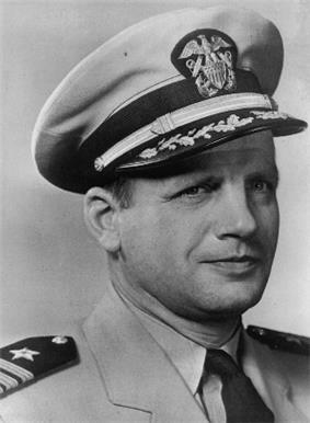 Head of a middle-aged man wearing a light-colored jacket with stripes and a star on shoulderboards, a dark colored tie, and a peaked cap with decorative leaves on the visor.