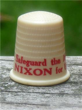 Beige thimble with red lettering, the visible part of which says