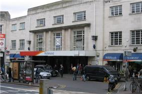 A grey building with a rectangular, white sign reading