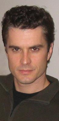 A man with dark hair, wearing a brown sweater and a black T-shirt.