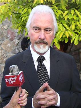 A photo of a bearded man being interviewed by another person holding a microphone. He is wearing a black suit and tie and a white shirt.