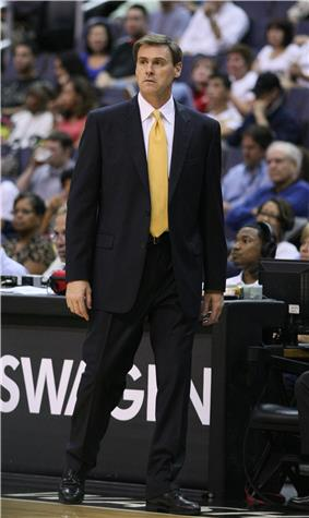 A man wearing a black suit is standing on the side of basketball court.