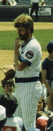 A bearded man in a white baseball uniform with blue pinstripes holds his left hand below his mouth.