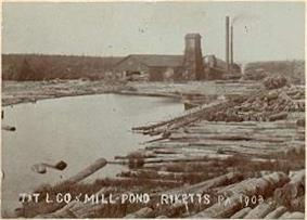 Sepia-tone photo of a pond surrounded by large logs. At the far end of the pond is a large building with a square tower and two smokestacks. Label is