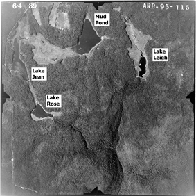 Black and white aerial photo of four lakes (labeled per the caption) with a deep Y-shaped valley at bottom. The photo is labeled at top: