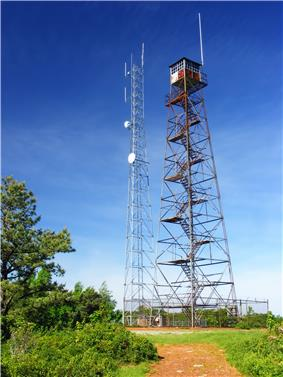 Photo of two towers that appear side by side. The tower on the left is shorter and has several discs on its side. The tower on the right has zig zag stairs going up the middle with a hut on top. Green trees appear on the right foreground with a blue sky in the background.