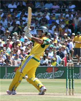 A man in a cricket uniform swinging the bat at a sports ground. A crowd watches in the background.