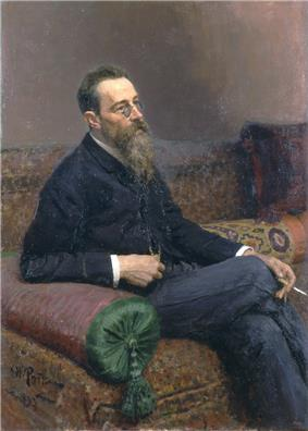 A man with glasses and a long beard sitting on a sofa, smoking.