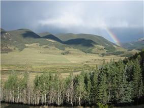 A small river winds through mountains under a rainbow.