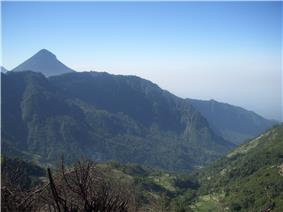 Looking from the ridgeline down into the old volcanic edifice, with the peak of Volcan Santa Maria in the background.