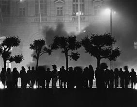 A black and white photograph of dozens of people standing in silhouette with City Hall in the background; something is on fire and smoke is obscuring part of the building