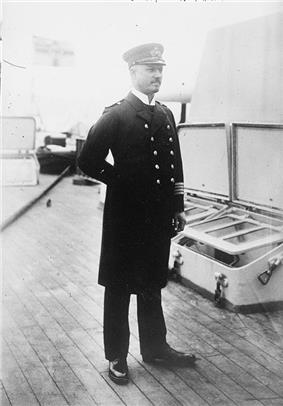 A standing man in naval uniform.