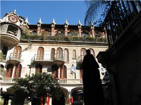 Photograph in a courtyard at the Mission Inn, with four floors of Spanish revival architecture, arches, and tile roofs rising overhead.