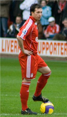 A man dressed all in red standing with his hands on his hips and his left foot on a yellow ball