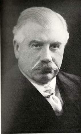 head and shoulders photograph of a middle-aged man with large, curled moustache