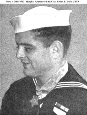 Profile of a young white man wearing a white sailor's cap and a dark sailor suit. A star-shaped medal hangs from a wide ribbon around his neck.