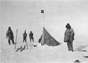 Four figures in heavy clothing stand near a pointed tent on which a small square flag is flying. The surrounding ground is ice-covered. Ski and ski poles are shown on the left.