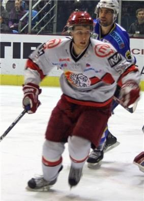 An ice hockey player skating towards the camera. He is wearing a red helmet and a red and white uniform.