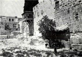 a black and white photograph showing a patch of rough ground with a stone wall running along the right side and a series of stones sticking out at the bottom of the wall in the foreground, partially obscured by a shrub