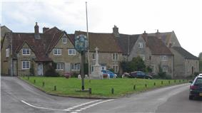 Street scene. Triangular area of grass with village sign on wooden post and stone cross behind. Stone houses with tiled roofs n the background.