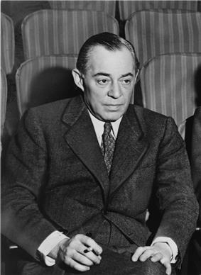 Photo of Rodgers, in middle age, seated in a theatre, wearing a suit and holding a cigarette