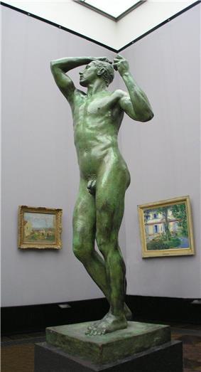 Life-sized nude stature of a male on a pedestal on display in a museum.
