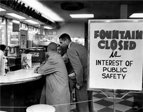 Lunch counter with four young black men seated at bar stools along the counter. They are not being served and are simply sitting. A sign on the checkerboard-tiled floor reads