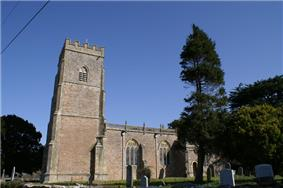 Stone building with square three stage tower at the left hand end. Trees to the right hand gravestones in front.