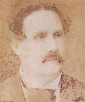 Faded sepia photograph showing the head and shoulders of a man with dark, wavy hair, mustache and wearing a dark coat, white shirt with wingtip collar and dark cravat
