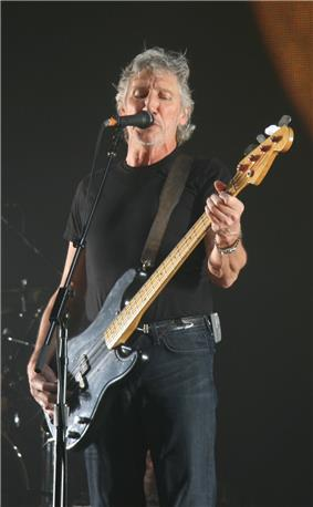 Roger Waters playing a bass guitar and singing into a microphone. He has grey hair and is unshaven.