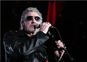 Waters on stage wearing sunglasses and a black leather coat. He is holding a microphone up to his mouth.