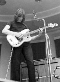 A monochrome image of Waters playing bass guitar. He has shoulder-length hair, black attire, and is standing in front of a microphone.