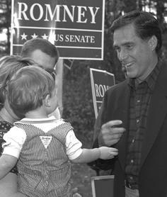 Man smiling at right with sign in background and parents holding toddler at left