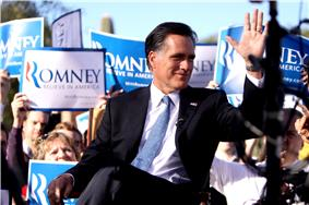 Mitt Romney sitting outdoors during daytime, with crowd behind him holding up blue and white