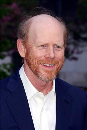Portrait of a balding, red-haired Caucasian male who is wearing an unbuttoned white collared shirt over a blue suit.