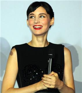A smiling woman with short hair wears a black dress.