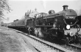 A side-and-front view of a 2-6-0 steam locomotive about to depart a railway station. The locomotive features smoke deflector plates either side of the boiler and there is a crew member oiling the motion. It is hauling four carriages.