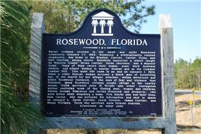 A color photograph of the front of the bronze plaque in Rosewood next to the highway