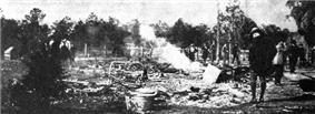 A black and white photograph of ashes from a burned building with several people standing nearby; trees in the distance