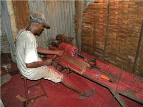 A man sits on a stool at a bench while using simple tools to spin a piece of rosewood while he carves it into a vase. Bright red sawdust covers the floor of this small rosewood vase factory.