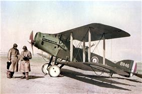 Two men in flying gear next to a military biplane