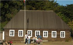 Photograph of the Fort Ross Commander's House on a sunny day. Visitors stand at a table in front of the rectangular log building with a high, peaked roof and white painted windowframes.
