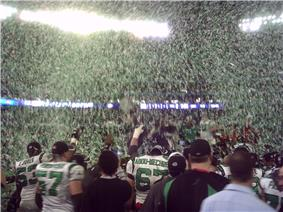 Green and white confetti floats through the air as several players and team staff celebrate a victory.