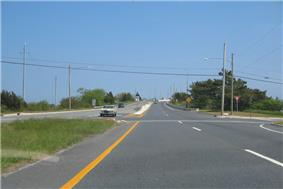 A four lane divided highway at an intersection approaching a drawbridge