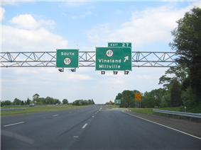 A four lane freeway at an interchange. Two green overhead signs stand over the road with the left one reading south Route55 and the right one reading exit27 Route47 Vineland Millville with an arrow pointing to the upper right