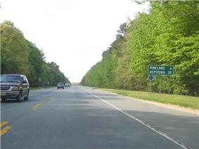 A two lane road running through woodland. A green sign along the road reads Vineland 6 Deptford 35